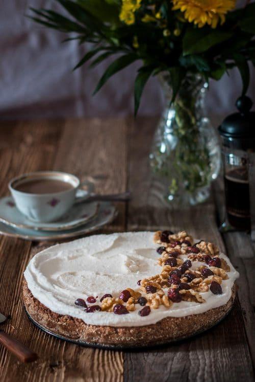 Kuchen mit weißer Glasur, Walnüssen und Cranberries auf einem Holzuntergrund und Kaffeegedeck
