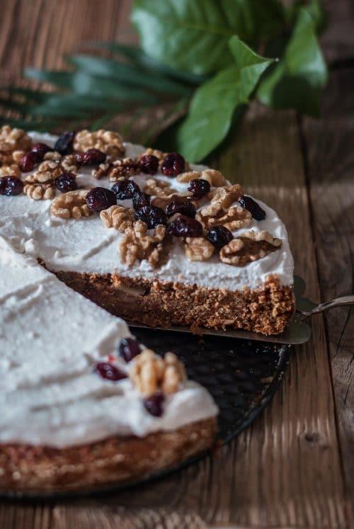 Kuchen mit Möhren, weißer Glasur, Walnüssen und Cranberries auf einem Holzuntergrund