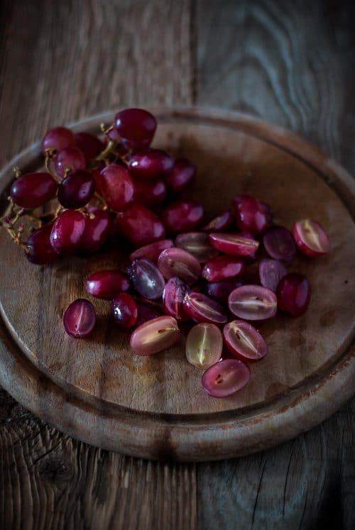 halbierte Weintrauben auf einem Holzbrett