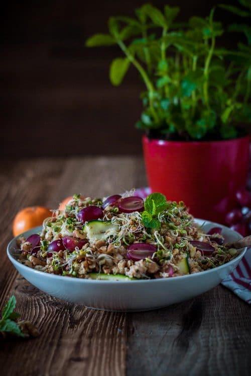 Schüssel mit Salat aus Bulgur, Weintrauben, Chicorée und Kichererbsen mit Minze auf einem Holzuntergrund