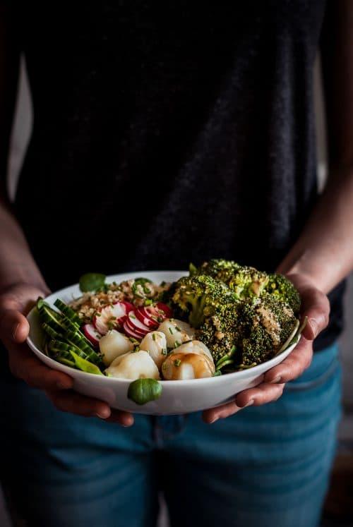 Buddha Bowl mit grünem Gemüse die in den Händen gehalten wird