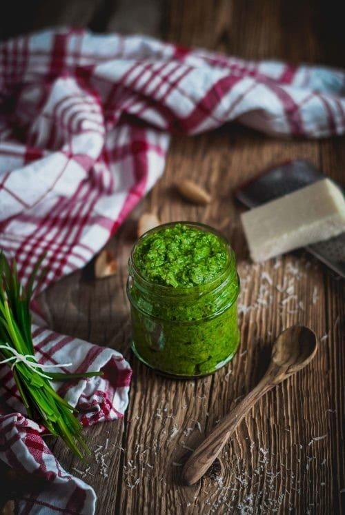 Ein Glas grünes Pesto auf einem Holzbrett