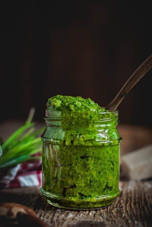 Ein Glas grünes Pesto mit Holzlöffel