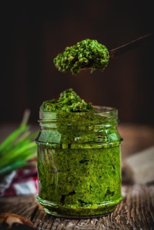 Ein Glas grünes Pesto mit einem Löffel Voll Pesto