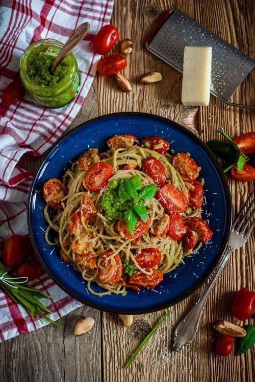 Ein Teller voll Spaghetti mit Tomaten und grünem Pesto auf einer Holzplatte