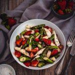 Salat mit Erdbeeren und Spargel auf einem weißen Teller mit Dekoration