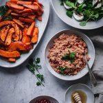 Orientalischer Couscous-Salat mit Ofengemüse und Salat auf einem Tisch