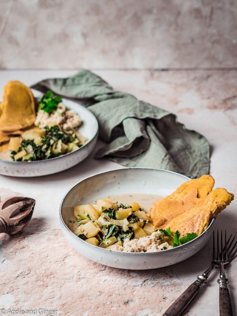 Kartoffel-Mangold-Curry mit Kokos-Chutney und Kichererbsen-Crêpes auf zwei Tellern