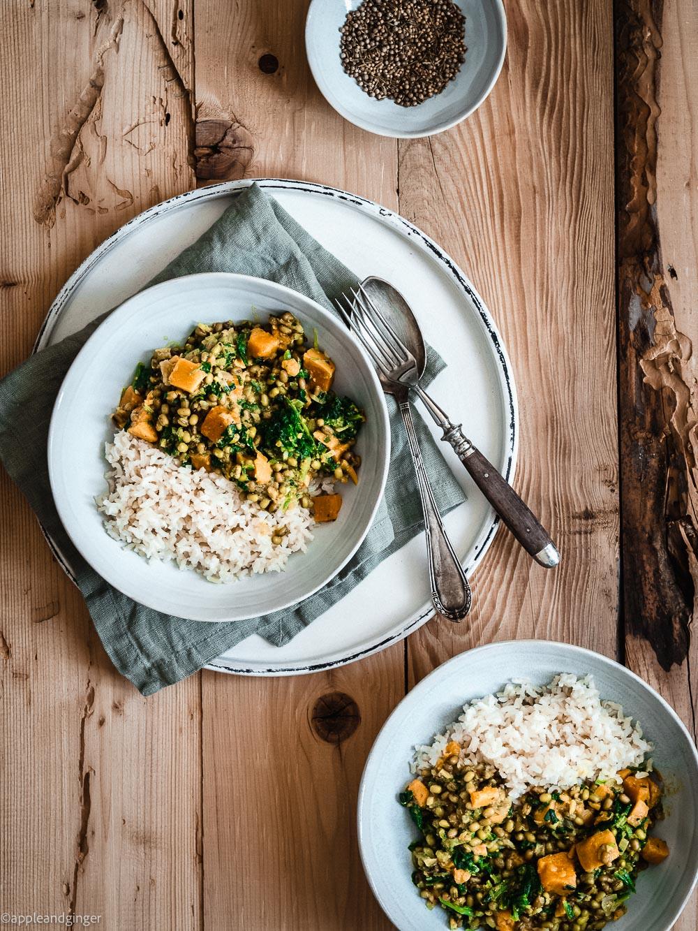 Mungbohnen Curry auf zwei Tellern auf einer Holzplatte