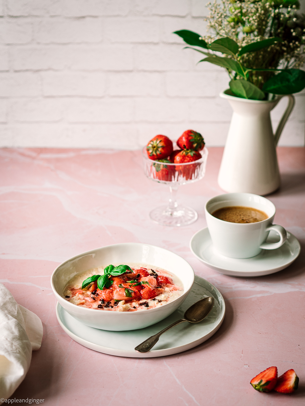 Milchreis mit Erdbeerlompott auf einem rosa Marmor Untergrund mit Kaffeetasse